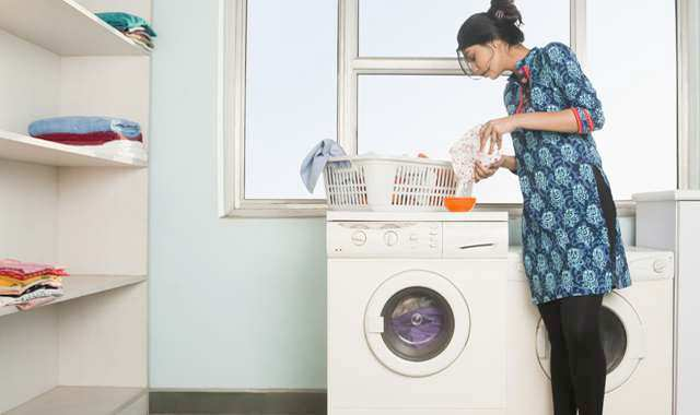 woman pouring laundry detergent near washer and dryer