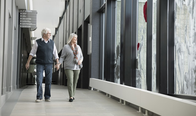 older couple holding hands and walking down a hallway
