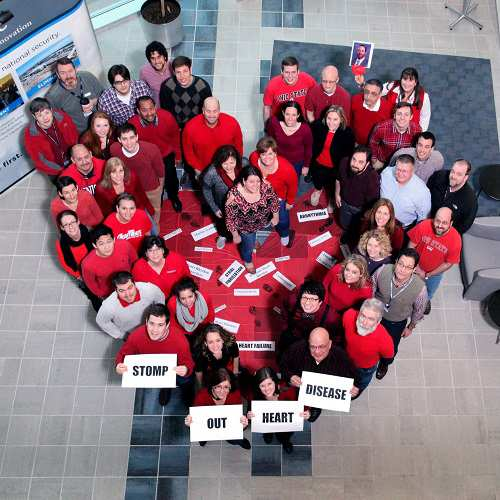 employees wearing red standing in the shape of a heart