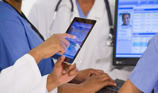 physicians reviewing data on a tablet and computer