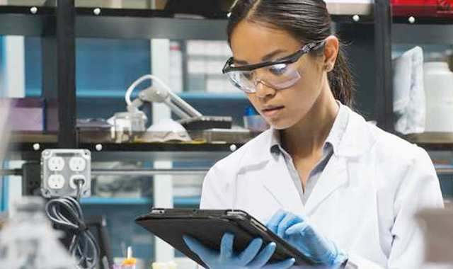 researcher in a lab working on a tablet