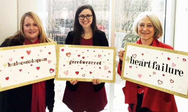 Members of the colloquium hold up signs showing hashtags to promote heart health