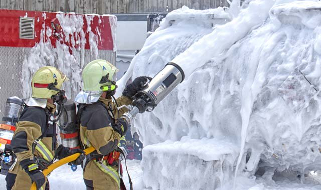 firefighters putting out a blaze using foam