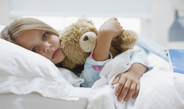 girl laying in hospital bed holding a teddy bear
